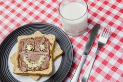 Milk and chocolate bread on the table. Closeup of yummy breakfast with a glass of milk and grated cheese shaped smiley face on chocolate breads Royalty Free Stock Image
