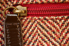 Closeup of a zipper in midst of woolen pattern texture material. Macro of a vivid red zip fastener on a bag with pattern of wool texture material royalty free stock photo