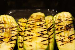 Closeup of zucchini grilled lying on a black frying pan royalty free stock photo