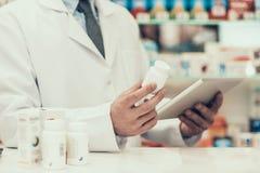 Closeupapotekare Holding Pills Bottle och minnestavla arkivbild