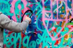 Closeuparm av den unga grabben som drar färgrika grafitti på väggen Modern kultur för begrepp royaltyfri fotografi