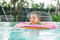 Closeupasiatet behandla som ett barn pojken sitter i ett fartyg för barn i simbassängbakgrunden med leendeframsidan i lycklig sin arkivfoto