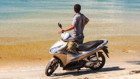 Closeupbaken Guy Stands med mopeden beundrar havet på stranden arkivfilmer
