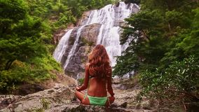 Closeupbakflickan i baddräkt i yoga poserar vid vattenfallet arkivfilmer