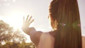 Closeupbaksidasikt av en kvinna som ser solen och döljer sig från solen med hennes hand Ung kvinna med fruktaner arkivfilmer