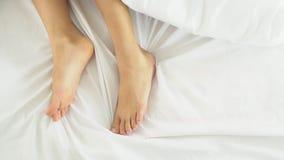 Closeupben och fot av kvinnasömn under flyttande gyckel för filt på säng i sovrummet stock video
