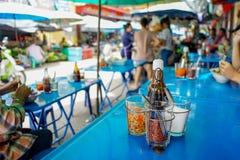 Closeupbild av den kryddiga nudeln med soppa i en keramisk bunke med suddigt folk som äter nudeln i bakgrund Läcker gatamat fotografering för bildbyråer