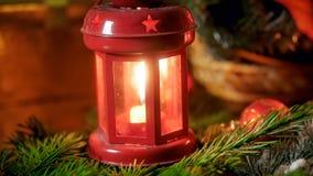 Closeupbild av den röda dekorativa lyktan med bränningstearinljuset på brandträdfilial Perfekt backgorund för vinterferier royaltyfri bild