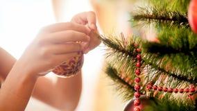 Closeupbild av den tonårs- flickan som smyckar julgranen royaltyfri bild