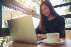Closeupbild av en härlig asiatisk affärskvinna som ser, arbetar och skriver på bärbar datortangentbordet med koppen för vitt kaff royaltyfria bilder