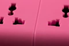 Closeupbild av ett rosa uttag på svart. Arkivfoto