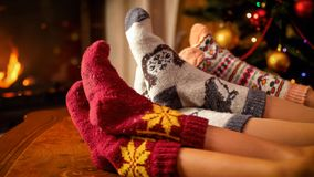 Closeupbild av familjen i varma stack sockor som ligger bredvid spisen och julgranen arkivbilder
