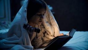 Closeupbild av flickan som ligger i säng och läsebok en tnight royaltyfri bild