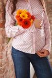 Closeupbild av gravida kvinnan som trycker på hennes buk med händer Den unga gravid kvinnainnehavgruppen av ljus sommar blommar royaltyfri fotografi