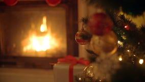 Closeupbild av guld- och röda struntsaker på julgranen Brinnande spis på bakgrunden arkivfilmer