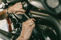 Closeupbild av motorcykelmekanikern som reparerar motorcykeln i billager Fotografering för Bildbyråer