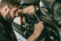 Closeupbild av motorcykelmekanikern som reparerar motorcykeln i billager Arkivfoto
