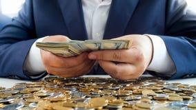 Closeupbild av rikt ungt affärsmansammanträde bak tabellen som täckas med pengar och räknas bunten av dollar arkivbilder