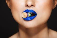 Closeupbild av sexiga färgrika kanter för kvinna` som s rymmer raringar med tänder Över grå färgbakgrund royaltyfri foto