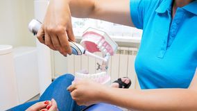 Closeupbild av tandläkarevisningpatienten hur man använder den elektriska tandborsten Arkivfoton