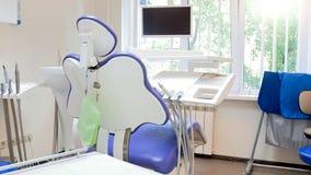 Closeupbild av tom tandläkarestol och medicinsk utrustning i modern klinik royaltyfri fotografi