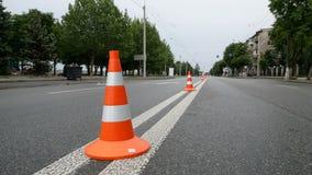 Closeupbild av trafiktecknet - orange kotte med vita band på bakgrund för stadsväg lager videofilmer