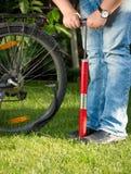 Closeupbilden av den unga mannen som pumpar det plana cykelhjulet på, parkerar Arkivfoto