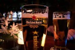 Closeupbilden av ett exponeringsglas av öl med det Heineken märkestecknet exponerade royaltyfria bilder