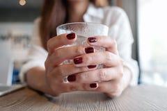 Closeupbilden av händer för kvinna` s med rött spikar färg som rymmer ett exponeringsglas royaltyfria foton