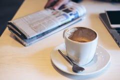 Closeupbilden av kaffekoppen, tidningen, bärbar dator och ilar telefonen på trätabellen royaltyfria foton