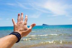 Closeupbilden av mans handen på havsbakgrund Royaltyfria Bilder