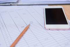 Closeupblyertspenna med den finansaffärsarket och telefonen äganderätt för home tangent för affärsidé som guld- ner skyen till Arkivfoto