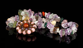 Closeupbrosch och pärlor från kristaller av ametist, fluorite, jaspisen, karneolen och rosa kvarts på svart akryl Royaltyfria Bilder