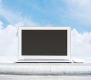 Closeupdatoranteckningsbok med musen på cementskrivbordet i parkera med härlig utrymmebakgrund för blå himmel i arbetsbegrepp på  Royaltyfri Foto