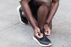 closeupdetalj Mannen binder upp skosnören på gymnastikskor för körning fotografering för bildbyråer