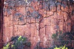Closeupdetaljen eller bakgrund av rött vaggar klippan med sprickor och stora bitar och lite vegetation arkivbilder