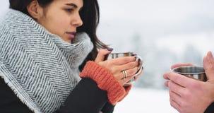 Closeupdetaljer av turist- drink två någon varm drink från järnkoppen, i överkanten av berget, kalla röda händer som de har stock video