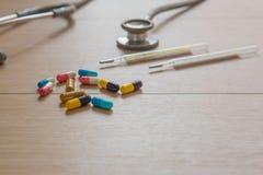 Closeupdrogkapsel och stetoskop och kvicksilver på den Wood tabellen MEDICINSKT begrepp fotografering för bildbyråer