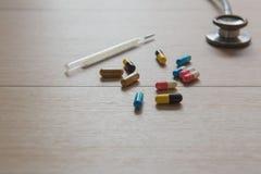 Closeupdrogkapsel och stetoskop och kvicksilver på den Wood tabellen MEDICINSKT begrepp royaltyfri bild