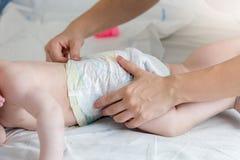 Closeupen av att ändra för barnmoder som är hennes, behandla som ett barn blöjan för pojke` s Arkivfoton