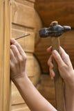 Closeupen av att bulta för händer spikar i planka royaltyfria foton