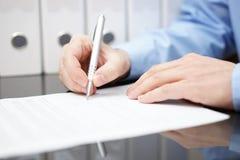 Closeupen av bussinessmanen undertecknar avtalet med dokumentation I Royaltyfria Foton