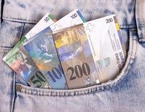 Closeupen av de schweiziska anmärkningarna i jeansen stoppa i fickan arkivbild