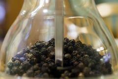 Closeupen av den glass pepparmolar maler med texturerade pepparkorn I Arkivfoton
