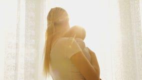 Closeupen av den härliga lyckliga modermodern med hennes behandla som ett barn pojkeanseende på det stora fönstret och att se sol arkivfilmer