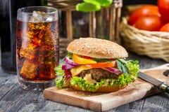 Closeup av den hemlagade hamburgaren och en cola med is Arkivfoton