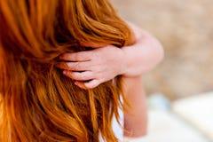 Closeupen av den lilla dottern räcker hållande hår för mamma` som s kramar i tecken av förälskelse och affektion Arkivfoto