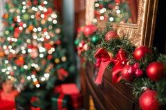 Closeupen av den röda och gröna struntsaken som hänger från dekorerad jul, förgrena sig Abstrakt bakgrund med defocused ljus Royaltyfria Bilder