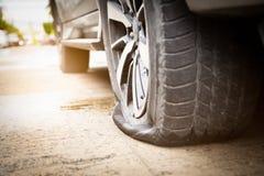 Closeupen av det plana gummihjulet för bilhjulet på vägen, läcka för bilgummihjul på grund av spikar att dunka på den väntande på arkivfoton