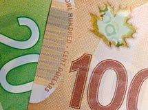 Closeupen av dollarräkningen för kanadensare som 20 överlappar kanadensiska 100 gör Arkivfoto